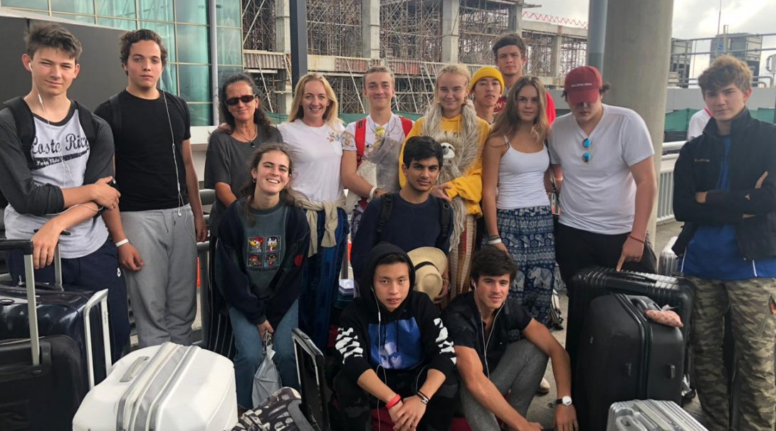 A group of 16 year olds at the airport preparing to head home after volunteering abroad.